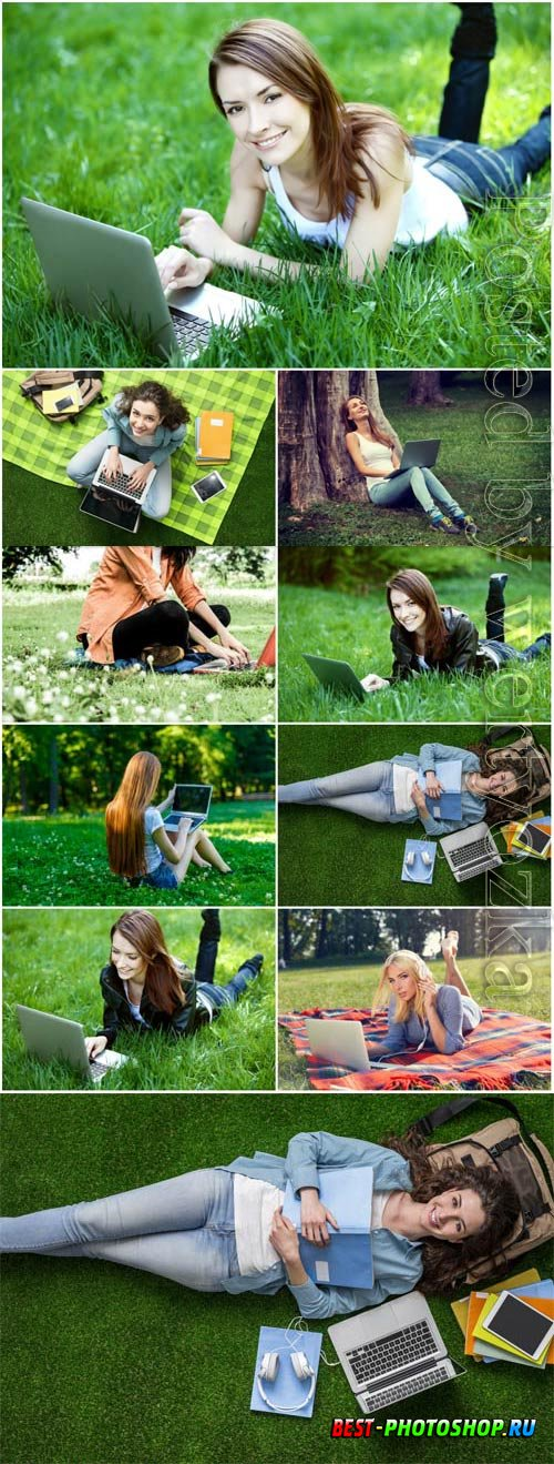 Girls with laptop lie on green grass stock photo